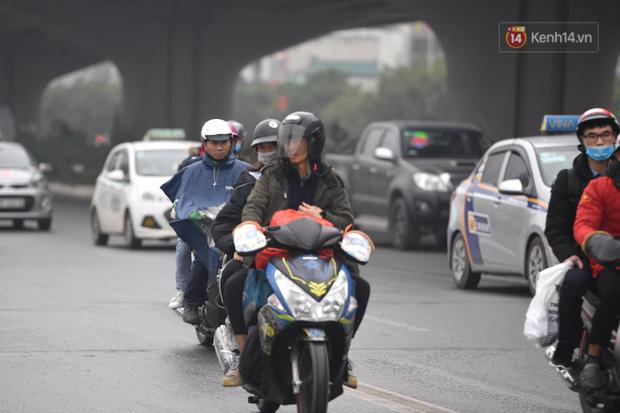 Trẻ nhỏ trùm chăn, khoác áo mưa chật vật theo chân bố mẹ rời Thủ đô về quê ăn Tết - Ảnh 2.