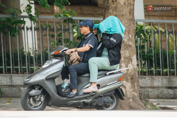 Nhiệt độ ngoài đường tại Hà Nội lên tới 50 độ C, người dân trùm khăn áo kín mít di chuyển trên phố - Ảnh 18.