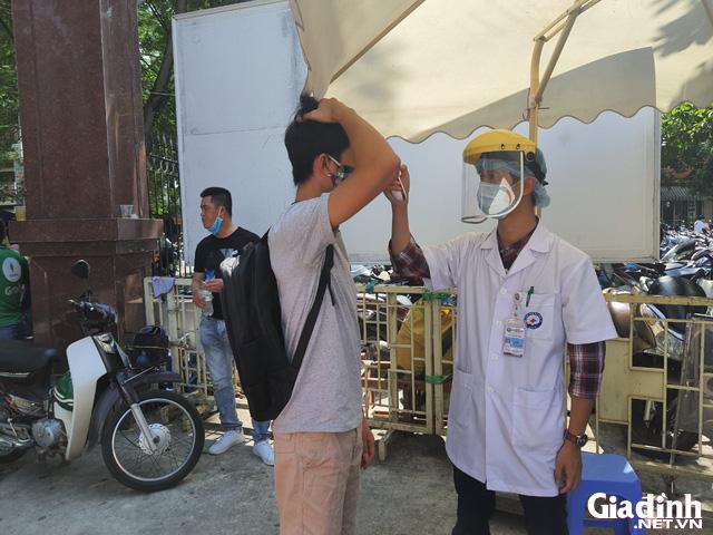 ẢNH: Người dân khai báo y tế bắt buộc, đo thân nhiệt khi đến bệnh viện - Ảnh 4.