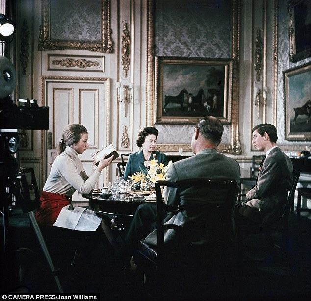 Time for tea: Anne may be reading, but its hardly a relaxed family meal for her, the Queen, Philip and Charles, with jackets, ties, napkins, bone china, a vast choice of glasswear and a floral display in the centre of the table