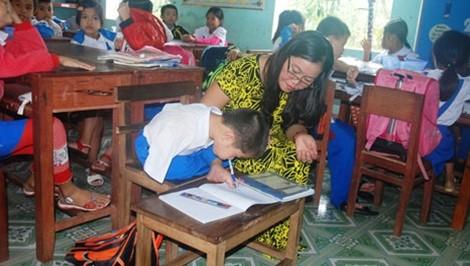 Cô giáo Sành đang giúp em Tài viết chữ. Ảnh: Công An Nhân Dân.