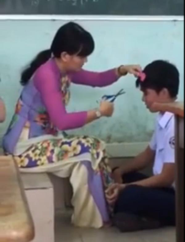 Cô giáo cắt tóc cho học trò - Ảnh chụp từ clip.
