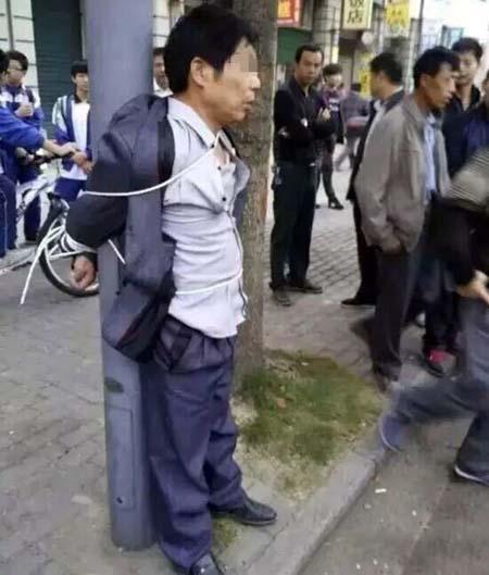 Xu bị trói vào cột đèn trước sự chứng kiến của rất nhiều người qua đường. Ảnh: CEN