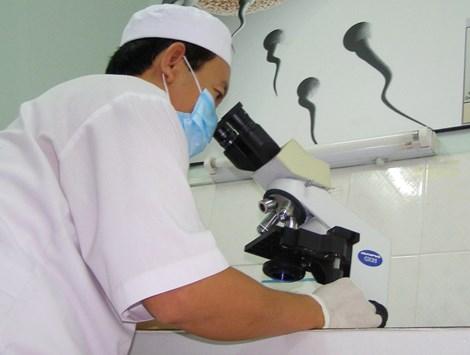 Nhân viên y tế kiểm tra phôi được thụ tinh trong ống nghiệm của một cặp vợ chồng. Ảnh: TRẦN NGỌC