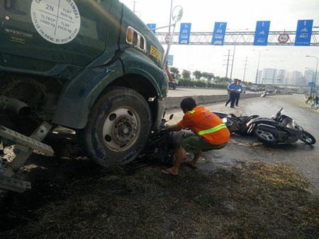 Dầu nhớt đổ lênh láng ra mặt đường khiến nhiều chiếc xe máy bị trượt ngã. Người dân tạm khắc phục bằng cách phủi vụn cỏ lên trên - Ảnh: Công Nguyên