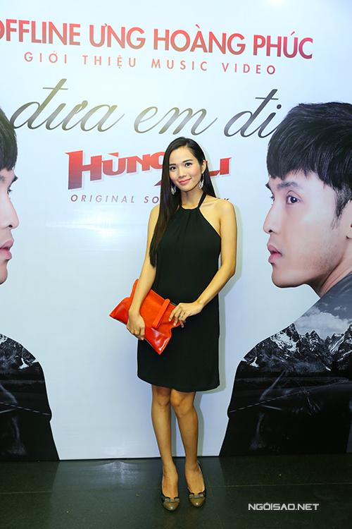 Kim Cương đang mang thai được khoảng 4 tháng. Giải đồng Siêu mẫu mặc váy đen, lấy túi che bụng khi tạo dáng trước ống kính.