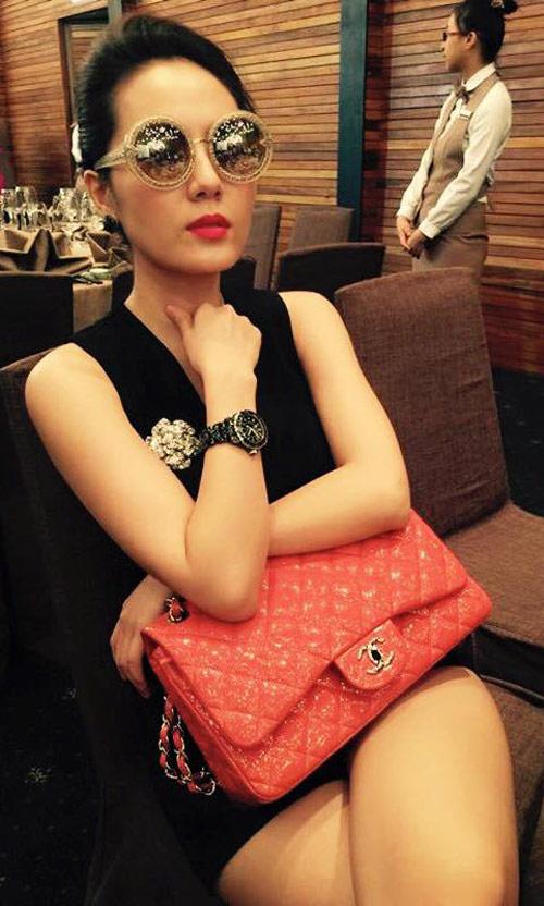 Túi Chanel 2.55 gam đỏ trở thành điểm nhấn ấn tượng trên nền trang phục đen. Nó được yết giá 4.500 USD (khoảng 100 triệu đồng). Chiếc cài áo đính đá hình bông hoa cũng thuộc thương hiệu danh tiếng nước Pháp.