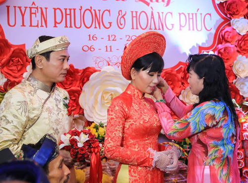 Chị của nam diễn viên thay mặt mẹ đã khuất trao hoa tai cho cô dâu.