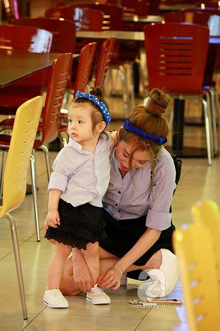 Cô ngồi bệt để cột lại dây giày cho bé