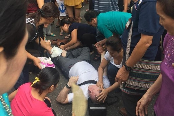 """Người dân Hà Nội """"sơ cứu"""" cho người đàn ông nước ngoài bị ngất trong phố cổ. Ảnh: Trịnh Gia Bách"""