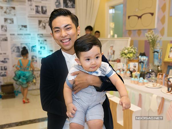 Tối 17/7, Phan Hiển - Khánh Thi tổ chức tiệc đầy năm cho con trai ở TP HCM. Trước giờ làm lễ, Phan Hiển bế con trai đứng đón khách. Gương mặt anh rạng rỡ, hạnh phúc.