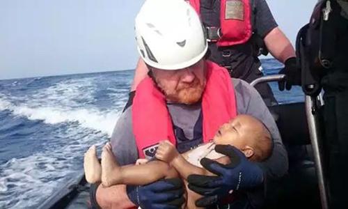 Nhân viên cứu hộ ôm thi thể em bé tị nạn trong tay. Ảnh: Sea-Watch