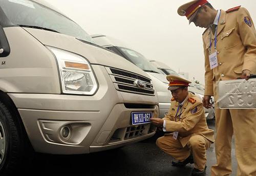 Cán bộ Cục Cảnh sát Giao thông, Bộ Công an lắp biển số tạm thời cho xe phục vụ Đại hội Đảng. Ảnh:Cục CSGT