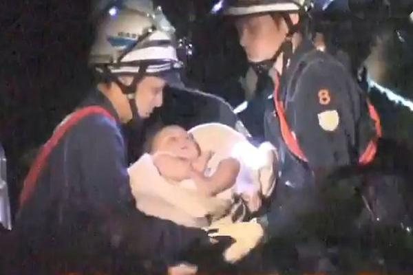 Bé gái may mắn được cứu sống sau đống đổ nát.