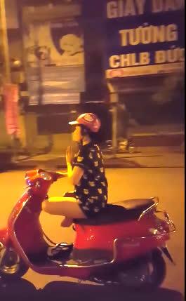Cô gái đi xe bằng 1 tay và khoanh tròn 2 chân trên yên xe.(Ảnh cắt từ clip)