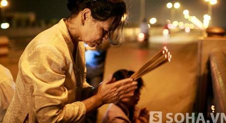 Bà Nguyễn Thị Hiền thắp hương bên cầu Thanh Trì nơi con gái bị ném xác xuống sông Hồng.