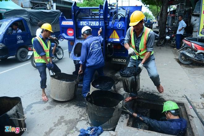 Một ngày làm việc của công nhân nạo vét cống bắt đầu từ 7h sáng đến 16h chiều. Những hôm mưa gió, các anh thay phiên nhau đi dọc những con đường hay bị ngập để dọn rác còn kẹt lại miệng cống giúp nước thoát nhanh.
