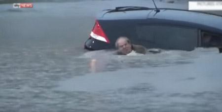 Một người đàn ông kịp thoát ra ngoài trước khi ôtô bị chìm trong nước lũ - Ảnh chụp từ video clip