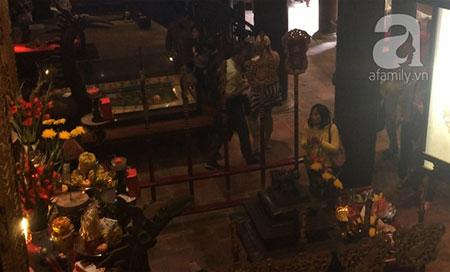 Người phụ nữ mặc áo vàng vừa chắp tay vừa đảo mắt nhìn tiền ở các bàn thờ.