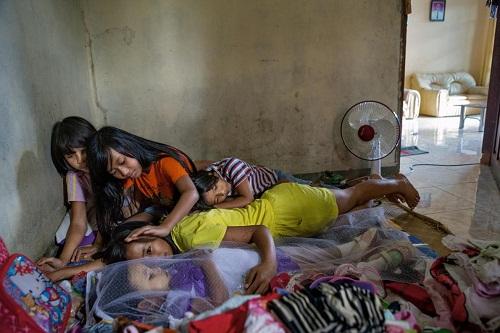 Chị em gái bên cạnh xác của Syahrini Tania Tiranda, bé gái 3 tuổi được phủ khăn voan mới mất một ngày.  Các bé ôm ấp và trò chuyện cùng Tiranda, coi em là makula - người ốm. Ảnh: NG