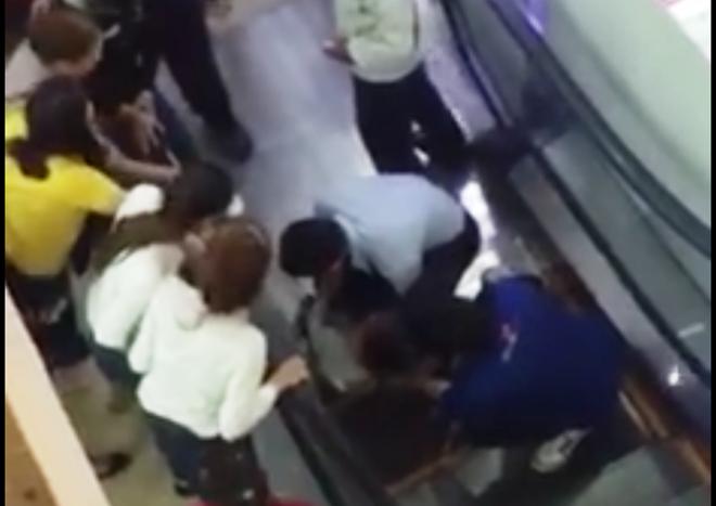 Nhân viên siêu thị đưa cháu Thành ra ngoài khi bị thang máy cuốn vào khe. Ảnh: Cắt từ clip.