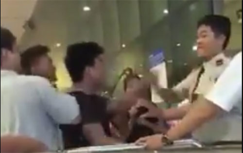 Người thanh niên (áo đen) chửi bậy, nhổ nước bọt vào nhân viên sân bay Tân Sơn Nhất. Ảnh cắt từ clip.