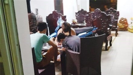 Trong một quán cầm đồ trá hình ở KTX Mỹ Đình, một nhóm sinh viên đang viết giấy cầm đồ. Ảnh: Tiền Phong.