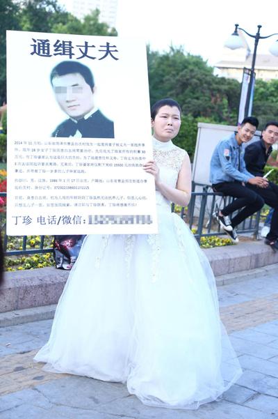 Ding giơ biển tìm chồng và hình anh ta với hy vọng tìm lại con trai 1 tuổi. Ảnh: QQ
