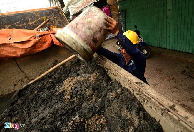 Không chỉ lo thoát nước, các công nhân còn phải làm công việc vận chuyển bùn nặng nhọc lên xe chở đi ngoại thành xử lý.
