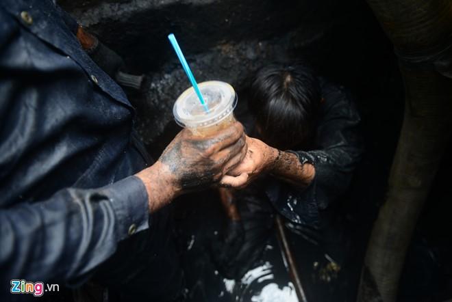 Một công nhân trèo lên uống vội hớp cà phê giải khát rồi chui xuống tiếp tục xử lý rác thải.