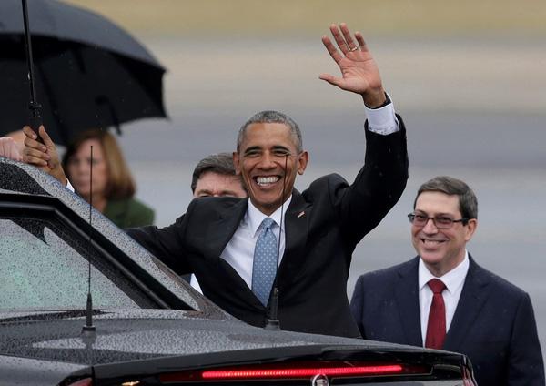 Bất chấp mưa gió, ông Obama vẫn niềm nở vẫy chào những người dân Cuba đứng xung quanh trước khi bước vào xe để rời sân bay. Ảnh: Reuters