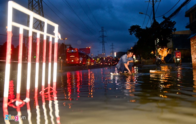 Cực nhất là lúc canh nước ngập vì có khi thức đến 22h tối còn chưa được về nhà. Anh Lê Thái Lộc ngồi trước miệng cống sau cơn mưa chiều 20/6 tại Kinh Dương Vương, quận Bình Tân.