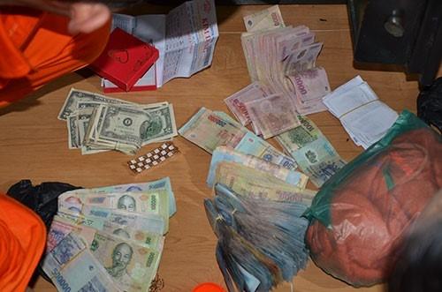 Lực lượng chức năng phát hiện 193 triệu đồng, 45 tép heroin cùng nhiều giấy tờ liên quan việc buôn bán ma túy trong nhà bà Lợi. Ảnh: H.Lê.