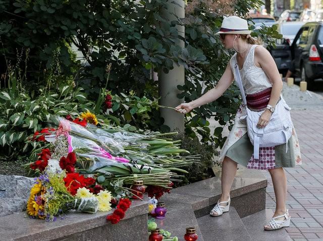 Một người phụ nữ đặt hoa tưởng niệm các nạn nhân ở Nice. Ảnh: Reuters