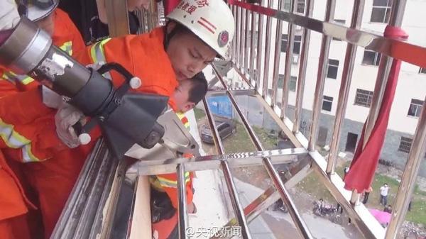 Các chiến sỹ cứu hóa dùng thiết bị chuyên dụng cắt thanh sắt của lan can để bế bé trai ra khỏi đó.