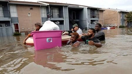 Người dân một khu chung cư ở Houston sơ tán khi nước lũ dâng cao - Ảnh: AP