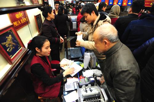 Nhân viên thu ngân của các hàng vàng nhận tiền mỏi tay trong ngày vía Thần Tài. Ảnh:Giang Huy.