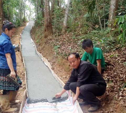 Phó Chủ tịch UBND xã Hoàng Thu Phố - anh Tráng Seo Pao - cùng người dân làm đường bê tông (Ảnh TL)
