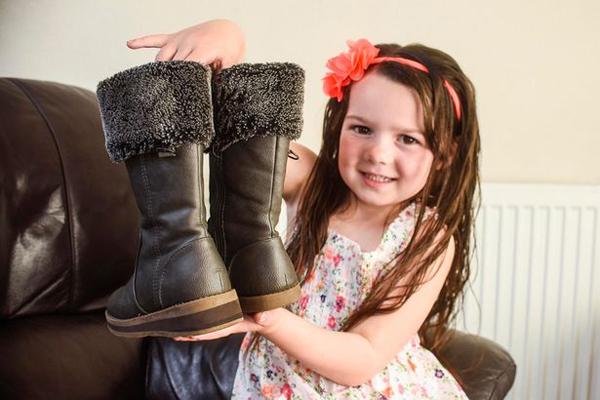 Cô bé 5 tuổi khoe đoi giày bên cao bên thấp. Ảnh: Mercury Press