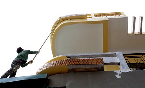 Nhiều hộ gia đình ở mặt đường Lê Trọng Tấn tất bật sơn mặt tiền thành màu vàng để đồng bộ trên cả tuyến phố. Chi phí chỉnh trang mỗi gia đình mất khoảng 10-20 triệu đồng. Ảnh: Bá Đô.