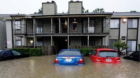 Một người dân đứng trên tầng hai nhìn nước lũ bao vây khu chung cư của mình hôm 18-4 - Ảnh: AP