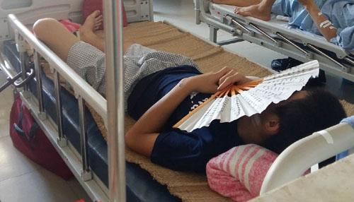 Nằm điều trị vết thương, Vi Văn Thắng lấy quạt che mặt để né tránh những người xung quanh.