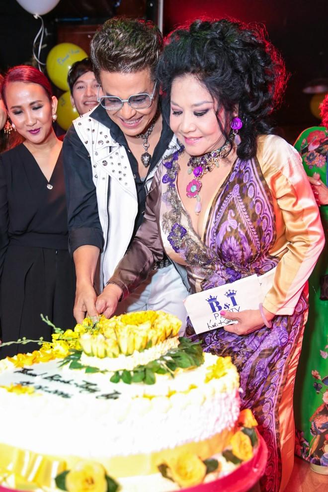 Chiếc bánh kem cỡ lớn được trang trí bằng hoa hồng và hoa lan màu vàng.