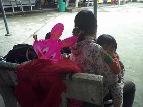 Một người mẹ ôm con chờ khám tại bệnh viện dịp Tết