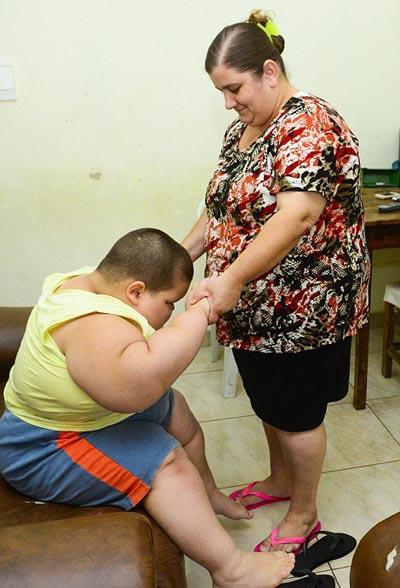 Mỗi khi đứng lên ngồi xuống cậu bé đều cần được trợ giúp.