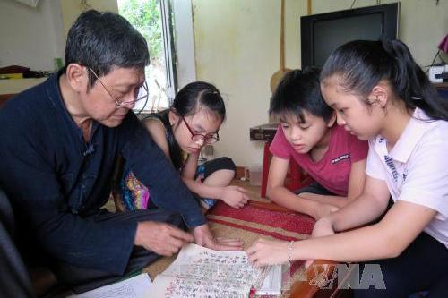 Nghệ nhân ThàmNgọc Kiến đang truyền dạy cho thế hệ trẻ các làn điệu Then truyền thống. Ảnh: Quang Đán