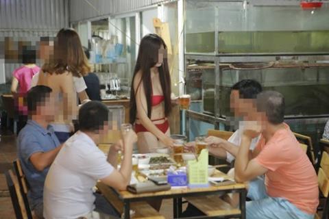 Những ánh mắt đồ dồn vào cơ thể của nữ nhân viên mặc bikini bán hàng. Ảnh: Facebook