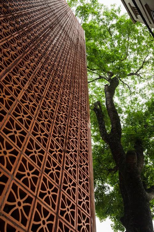 Hiện trạng mặt bằng cũng tạo nên thử thách cho đội thiết kế, chẳng hạn một cây lớn với tán lá rộng lớn che mặt tiền nhà. Các kiến trúc sư đã biến cây trở thành một phần của công trình với màu xanh của cành lá nổi bật trên nền gạch nâu đỏ.