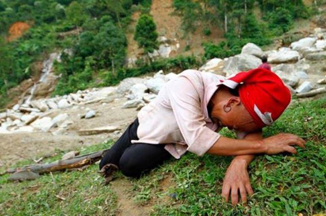Bên những tảng đá, bãi bùn, người phụ nữ dân tộc Dao đỏ (xã Phìn Ngan, huyện Bát Xát) gào khóc khi người thân, nhà cửa bị lũ cuốn trôi rạng sáng 5/8. Ảnh: Nguyễn Nam