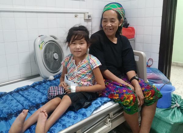 Nụ cười của mẹ con cô bé nghèo mắc quái bệnh trước khi xuất viện. Ảnh Vietnamnet.